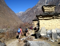 Trekkers walk by Mani wall